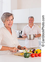 Old lovers preparing food in kitchen