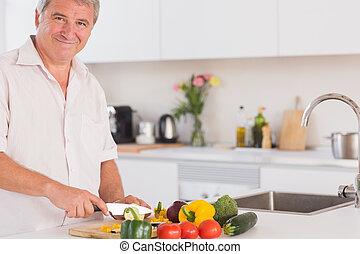 Old man smiling and preparing vegetables