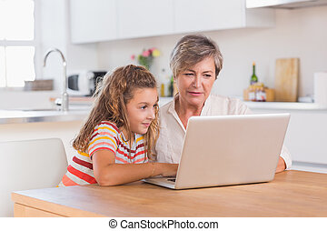 Child and granny looking at laptop in kitchen
