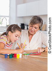 Child drawing with her grandmother in kitchen