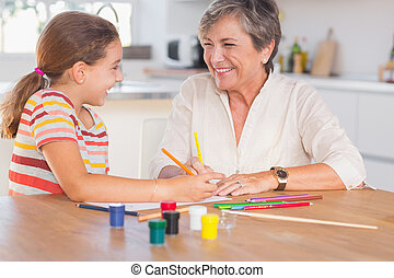 Child with her granny drawing and laughing in kitchen
