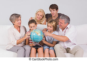 Family looking at globe on couch in sitting room