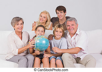 Family portrait looking at camera with a globe in sitting...