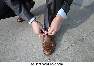 tying shoelaces - A businessman tying his shoelaces