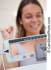 Scale showing dieting success to cheerful woman