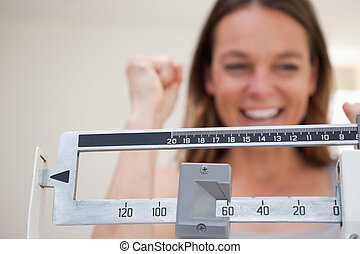 Scale showing weight loss to smiling woman