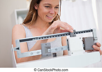 Woman adjusting medical scale for her needs