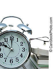 alarm clock with books on white background