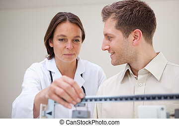 Doctor adjusting scale for her patient