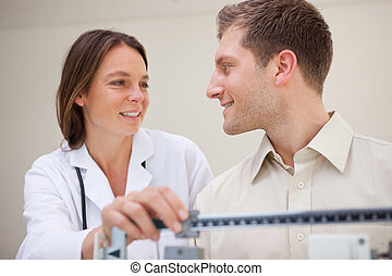 Doctor and patient talking about weight measuring