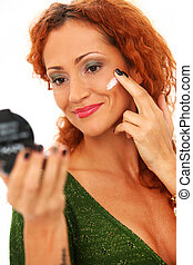 Beautiful redhead woman applying cream on a face