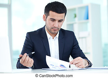 Paperwork - Portrait of serious businessman working with...