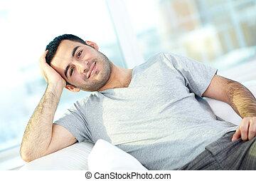 Man at home - A young man looking at camaera while relaxing...