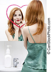 Redhead girl near mirror with heart it in bathroom