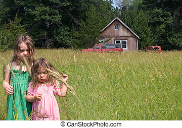 Abandoned - two little girls standing in a field in front of...