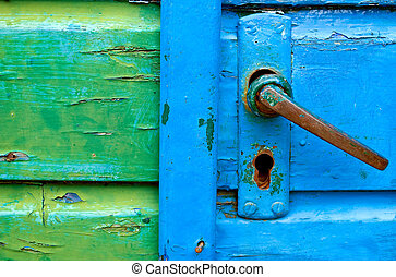 Old door handles close-up on blue and green wooden doors