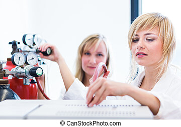 Two female researchers working in a laboratory color toned...