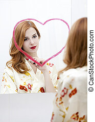 Redhead girl near mirror with heart it in bathroom.