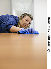 Professional female cleaner wiping table in office - Woman...
