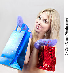 The young woman in  mittens with  packages rejoices to winter sale