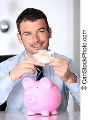 man in office with pink piggy bank