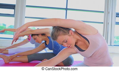 Video of women stretching on the fl