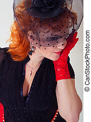 young woman with red hair in black hat with net veil