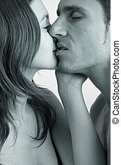 Closeup Kiss - Young adult couple in the studio kissing