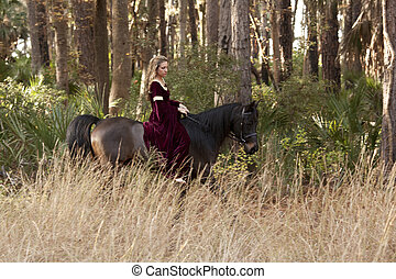 medieval woman riding horse through forest