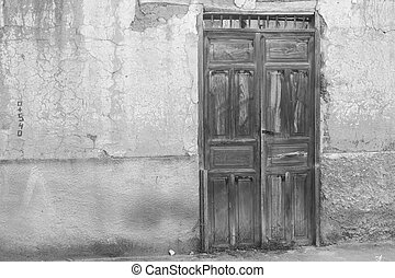 Black and white, old weathered wooden door in southern...
