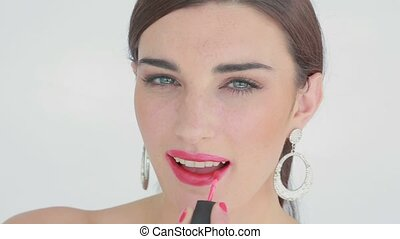 Woman applying pink lip gloss while smiling