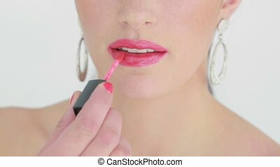 Woman applying pink lip gloss while having a porcelain face