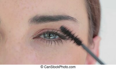 Beautiful woman's eyes getting made up with mascara
