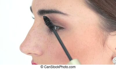 makeup artist applying mascara up on womans eyes