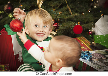 Cute Infant Mixed Race Baby and Young Boy Enjoying Christmas Morning Near The Tree.