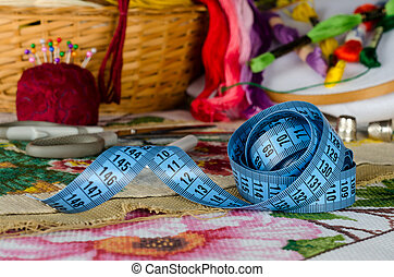 tapemeasure on a background set for cross-stitch -...
