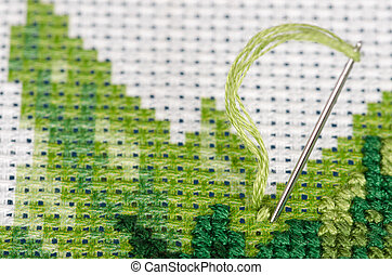 Cross stitching with a needle closeup - Cross stitching with...