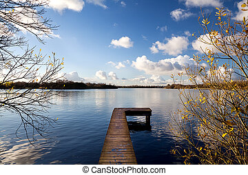 wooden pier on big lake in autumn - long wooden pier on lake...