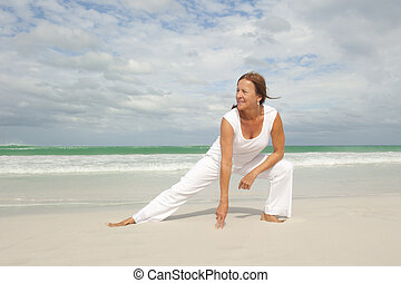Fit mature woman exercising beach isolated - Attractive fit...