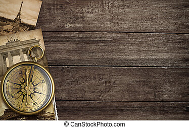 brass antique compass on table with old postcards and...