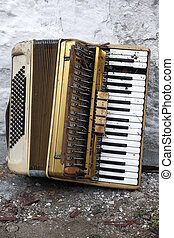 Old accordion - Damaged old accordion discarded on the...