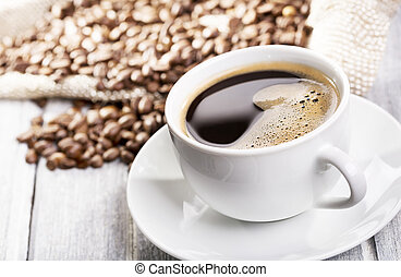 cup of black coffee and beans on wooden table