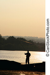 fisher - young fisherman fishing with sunrise in the...