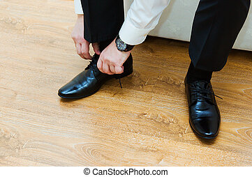 Man lacing up his black dress shoes