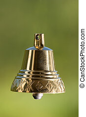 Handbell - Four brass handbell on a green background