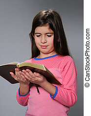 Young Girl Reading Bible - Young girl reading the Bible over...