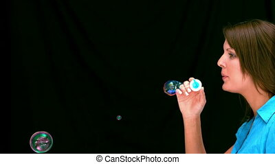 Brunette woman blowing bubbles