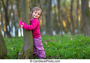 Cutl little girl hugging a tree trunk in the spring forest -...