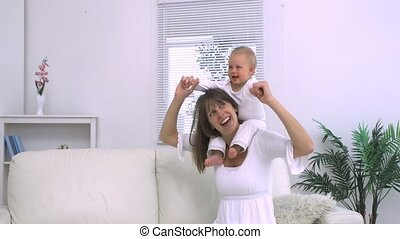Mother playing with her child on the shoulders in slow...