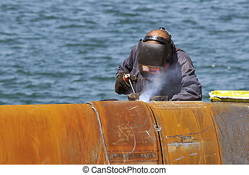 Industry - Worker welding two big pipes in a harbour